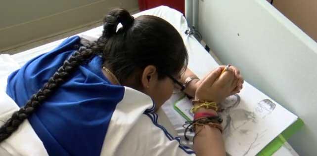 Quadriplegic woman creates art by holding pencil between her wrists